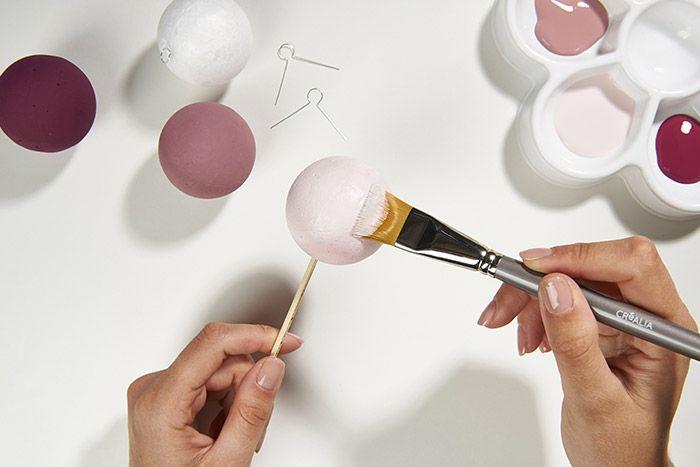 Peindre les boules avec les couleurs Rose poudré, Vieux Rose et Prune. Laisser sécher. Insérer les attaches métalliques. Garder quelques boules neutres à recouvrir complètement de ruban.