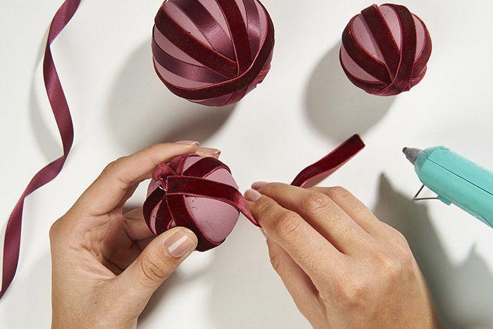 Idée n°2 : Couper des longueurs de différents rubans. Prévoir des bandes de 22 cm pour une boule de 7 cm et 16 cm pour une boule de 5 cm. Coller chaque bande de ruban autour de la boule en laissant des espaces régulier de peintures. Conseil : Pour l'utilisation d'un même ruban sur plusieurs tours, multiplier la longueur en fonction.