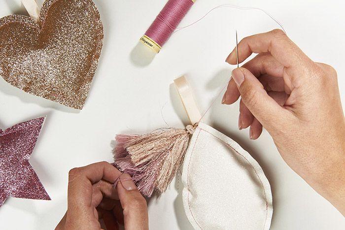 6. Coudre d'autres formes en variant les couleurs de tissus pailletés. Finaliser la suspensions feuillage avec un pompons cousu au sommet.