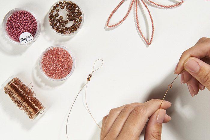 3. Enfiler trois perles cuivrées à facettes.