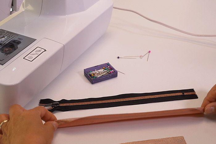 Pose de la fermeture éclair: Epingler endroit contre endroit la fermeture éclair contre le bord de ma pièce B (Tissu extérieur). Coudre au point droit à 1 cm du bord du zip avec le pied à fermeture à glissière. Répéter l'étape précédente sur l'autre côté du zip