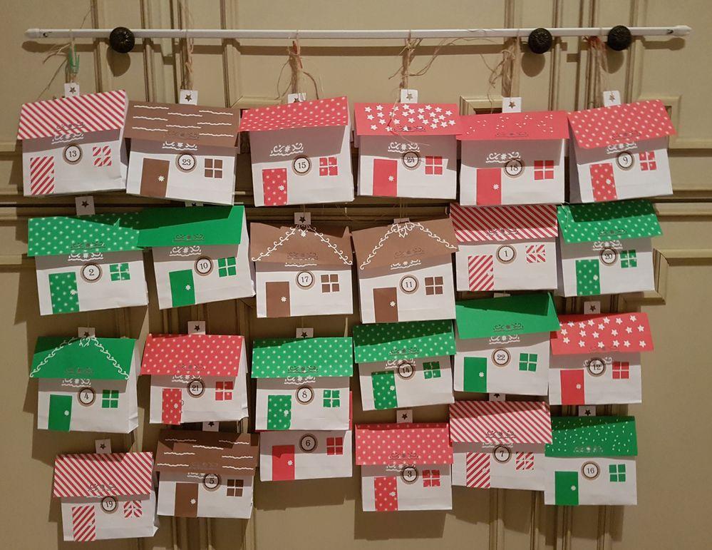 24 maisonnettes fabriquées à partir de pochettes découpées et décorées.  Les toits en papiers colorés sont glissés sur la cheminée.  Au dos une devinette ou un rébus. Pour voir la réponse il suffit d'ouvrir la porte. A l'intérieur des douceurs chocolatées.