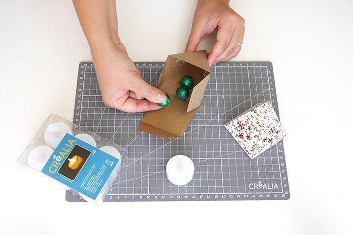ETAPE 7/9 Avant de fermer les boîtes complètement, vous pouvez y ajouter des bonbons, des petits mots doux ou même des bougies LED à l'intérieur pour un joli rendu illuminé.