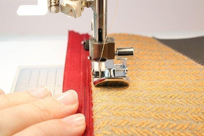 Trousse maquillage - étape 1 ETAPE 1/9 Téléchargez et imprimez le gabarit et découpez les pièces. Sur l'envers des tissus, reportez au feutre effaçable deux rectangles dans la feutrine et les deux triangles symétriques dans les simili cuir. Découpez les pièces.  Trousse maquillage - étape 2 ETAPE 2/9 Encoller les pièces de simili cuir avec la colle textile et positionnez-les sur le morceau de feutrine correspondant au devant de la pochette. Vous pouvez coudre les grands côtés des triangles au point zig-zag pour une jolie finition.  Trousse maquillage - étape 3 ETAPE 3/9 Posez l'endroit de la fermeture à glissière contre l'endroit de la feutrine. Le ruban de la fermeture à glissière est aligné au bord supérieur de la feutrine. Epinglez et cousez.  Trousse maquillage - étape 4 ETAPE 4/9 Retournez la feutrine sur l'endroit. Piquez à 5 mm du pli les 2 épaisseurs de feutrine et le ruban, afin de les maintenir en place. C'est ce que l'on appelle « surpiquer ».