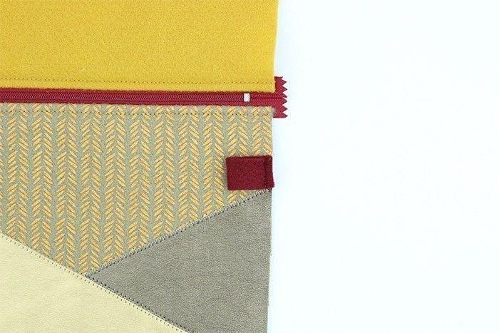 ETAPE 6/9 Découpez un rectangle de feutrine de 5 cm x 1,5 cm et pliez-le en deux. Cousez-le sur l'un côté de la trousse, le bord plié vers l'intérieur de la trousse.