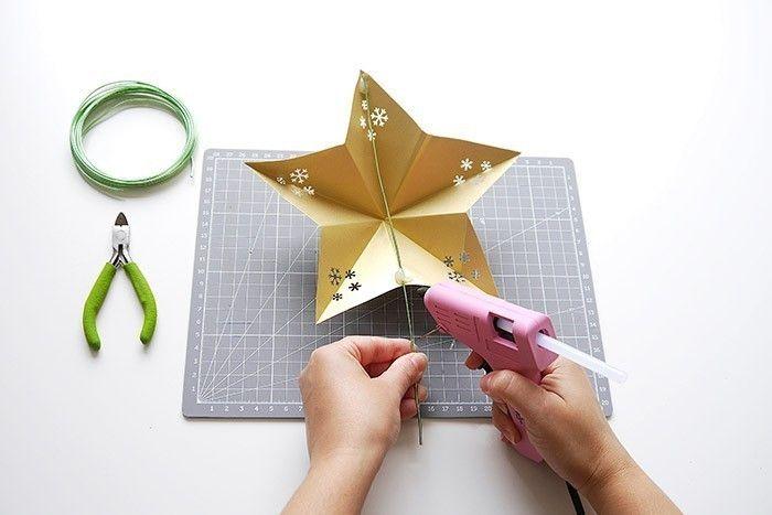ETAPE 15/16 Puis utiliser de la colle chaude et coller un morceau de fil de fer vert à l'arrière de l'étoile, afin de pouvoir l'accrocher au sapin.