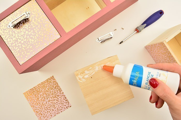 3. Coller les carrés de papiers sur les façades des tiroirs à l'aide de la colle blanche et revisser les porte-étiquettes.