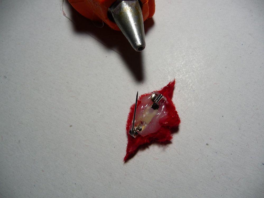 Affiner les contours en découpant délicatement avec des ciseaux fins afin de bien dessiner les lèvres. Coller une attache de broche au verso avec le pistolet à colle.