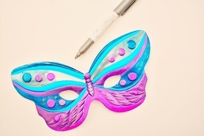ETAPE 4/5 Finaliser le masque en coloriant les zones restées blanches avec le feutre métallique argenté. Rehausser certains détails de petits traits argentée (corps du papillon …). Laisser sécher. Insérer et nouer une ficelle dans les trous de chaque côté du masque.
