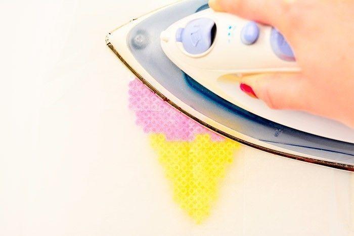 ETAPE 2/4 Positionner le papier à repasser et repasser jusqu'à voir les perles se souder entre elles (manipulation par un adulte). Attendre que les perles refroidissent un peu avant de retirer le modèle de la plaque transparente. Réaliser autant de gourmandises que souhaité en suivant ces deux étapes. Astuce : varier les couleurs si vous dupliquez certains modèles.