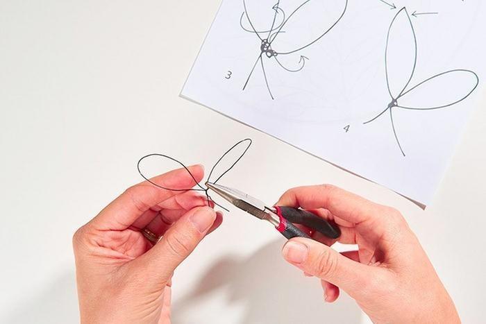 ETAPE 4/9 Pour le long feuillage, réaliser 8 duos de petites feuilles : créer une première grosse boucle et tourner les deux longueurs au point de raccord à l'aide de la pince plate. Appuyer au sommet de la boucle pour former deux feuilles rondes (voir schéma)