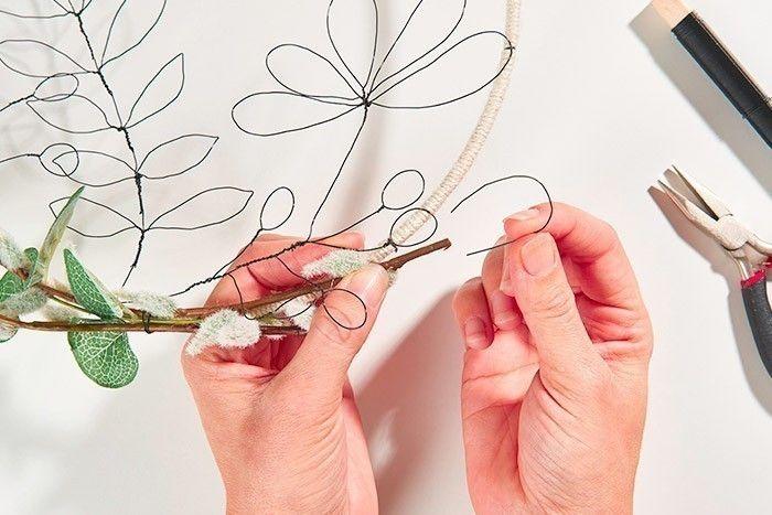 ETAPE 8/9 Positionner l'anneau sur le gabarit et fixer les différents éléments en fil de fer, à l'aide de petits morceaux de fil de fer torsadés. Finaliser la couronne végétale en fixant des branches de chatons et d'eucalyptus sur l'anneau, à l'aide de petits morceaux de fil de fer torsadés.