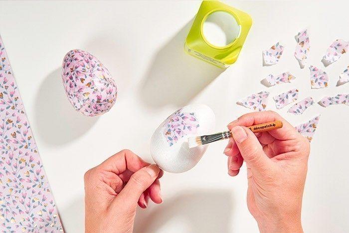 ETAPE 1/8 - DÉCORATION DES OEUFS Déchirer des petits morceaux dans le papier décopatch® choisi. Piquer l'œuf sur un pic en bois pour le maintenir facilement. Encoller la surface avec du vernis-colle. Positionner un morceau de papier décopatch® déchiré sur l'oeuf et repasser par-dessus une couche de vernis-colle, en veillant à bien lisser pour chasser les bulles d'air. Répéter cette action pour recouvrir tout l'œuf.