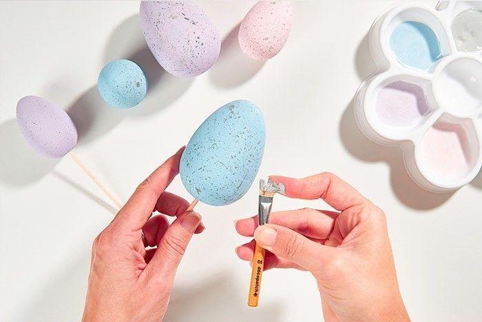 ETAPE 2/8 - DÉCORATION DES OEUFS Pour créer un effet « œuf de caille », peindre d'autres œufs avec les peintures du lot légèrement éclaircies de blanc pour obtenir des teintes pastels. Puis enduire un pinceau brosse de peinture grise légèrement éclairci de blanc et diluée à l'eau. Faire gicler la peinture en petites taches sur les œufs en grattant les poils du pinceau brosse. Laisser sécher.