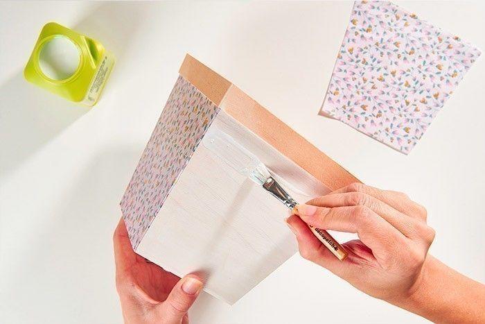 ETAPE 4/8 - DÉCORATION DU CACHE-POT EN BOIS Passer une sous-couche de gesso pour apprêter le support. Laisser sécher. Positionner une 1ère face du pot sur l'envers du papier décopatch® choisi, marquer son contour et répéter cette action pour chaque face. Découper et coller le papier décopatch® sur les 4 faces du cache-pot comme expliqué précédemment.