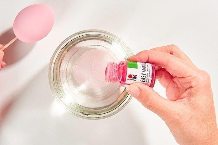 ETAPE 2/7 - EFFET MARBRÉ Dans un récipient de récupération rempli d'eau, verser 2 gouttes de peinture Easy marble Rose. Souffler dessus pour diffuser la couleur à la surface de l'eau.