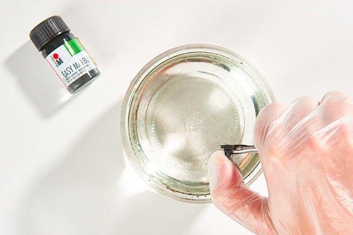 ETAPE 4/7 - EFFET MOUCHETÉ « ŒUF DE CAILLE » Enduire le pinceau brosse de peinture Easy Marble noire et mettre les gants de protection. Dans un récipient de récupération rempli d'eau, faire gicler la peinture en petites taches sur la surface de l'eau en grattant les poils du pinceau brosse.