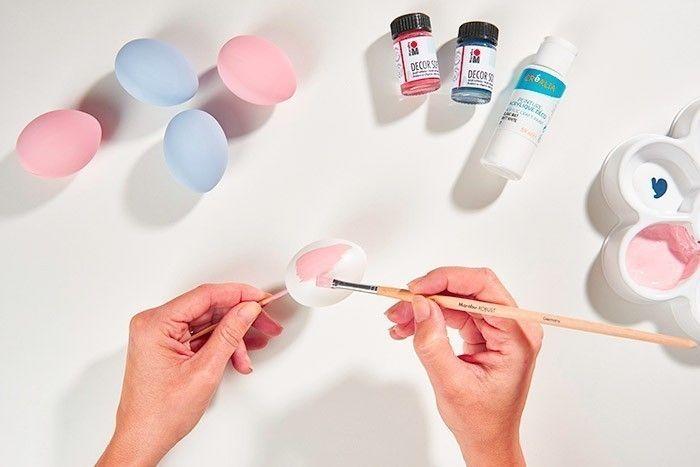 ETAPE 1/7 Pour obtenir des coloris pastels, mélanger 1/5ème de la couleur choisie à 4/5ème de peinture blanche du kit. Peindre les œufs avec ces coloris rose et bleu pastel. Laisser sécher. Astuce : S'aider d'un pic en bois pour faciliter le travail de peinture et le séchage.