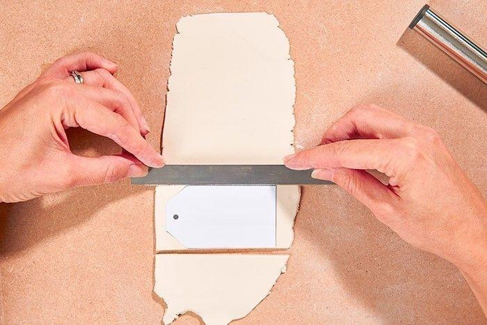 ETAPE 2/8 - DÉCOUPE DES ÉTIQUETTES Télécharger, imprimer et découper le gabarit de l'étiquette et la poser sur l'argile. Couper les débords à l'aide de la lame et percer le trou à l'aide d'un pic métal. Répéter cette action pour créer autant d'étiquettes que d'emballages cadeaux souhaités.