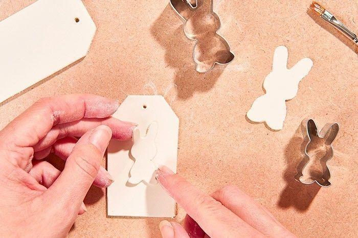 ETAPE 4/8 - TECHNIQUE DE L'APPLICATION Passer un peu d'eau sous le lapin découpé avec un pinceau puis le superposer sur l'étiquette en pressant légèrement.