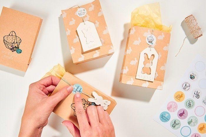 ETAPE 8/8 Garnir les emballages de papier de soie puis de surprises et les fermer avec une ficelle bicolore, l'étiquette en argile et un joli sticker. Les emballages sont prêts pour décorer votre table et gâter vos invités.