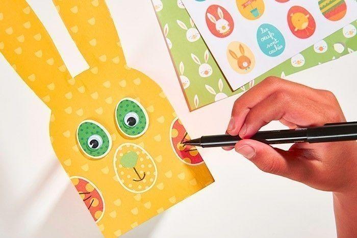 ETAPE 4/8 Couper un sticker « œuf » de la collection de papiers et les coller pour former les joues. Coller un autre sticker œuf au centre pour former le nez du lapin. Rehausser d'un petit morceau de papier vert pour former le museau. Dessiner au feutre noir les moustaches et la bouche.