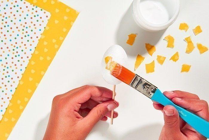 ETAPE 6/8 - DÉCORATION DES OEUFS Déchirer de tout petits morceaux de papiers de la collection. Encoller de vernis-colle la surface de l'œuf. Astuce : S'aider d'un pic en bois pour faciliter le travail de collage et le séchage.