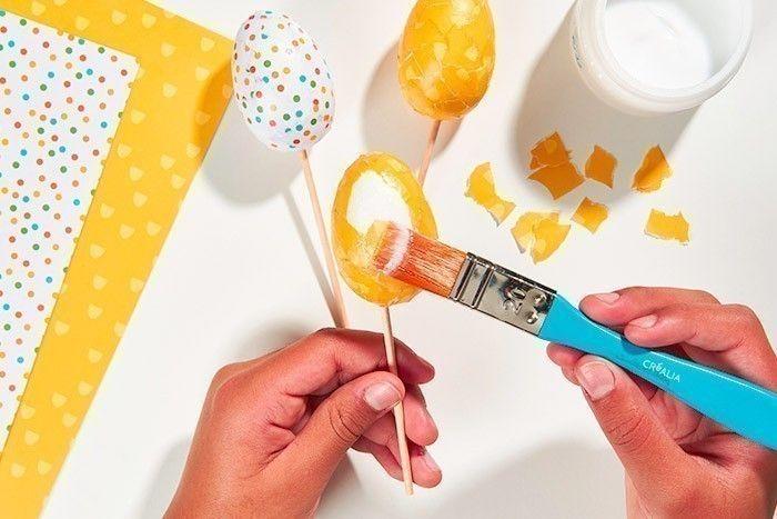 ETAPE 7/8 Poursuivre le collage sur toute la surface de l'œuf. Laisser sécher. Décorer tous les œufs de cette façon avec différents papiers de la collection. Astuce : humidifier le papier avec une éponge pour l'assouplir lors du collage.