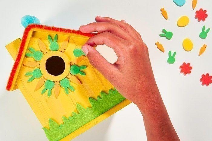 ETAPE 5/8 Pour créer une grande fleur sur la façade de la maison, coller les stickers « lapins » et « carottes » tout autour du hublot.