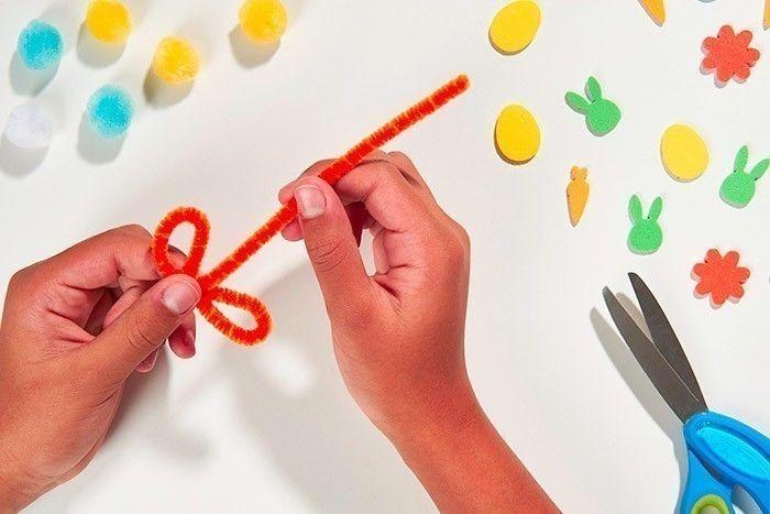 ETAPE 6/8 Sur le côté de la maison, créer une fleur : modeler le fil chenille pour former les pétales et la tige : créer une première boucle, tourner le fil chenille pour la fixer, puis créer une seconde boucle puis redresser pour former la tige. Coller sur la maison.