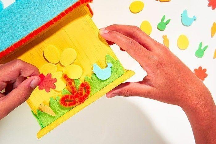 ETAPE 7/8 Coller ensuite 5 stickers « œufs » pour former les pétales de la fleur. Superposer un sticker « fleur » au centre. Terminer la décoration par des stickers collés dans l'herbe.