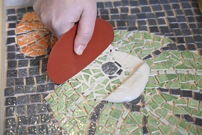 ETAPE 8/13 Préparer le joint en mélangeant 1/4 d'eau et 3/4 de poudre à joint. Avec l'estèque prendre du mélange à joint. Etaler le mélange sur l'ensemble de la mosaïque en veillant à ce que le joint pénètre partout. Astuce :  Ajouter 5 cuillères à soupe de fixateur pour remplacer le volume d'eau, cela imperméabilisera les joints