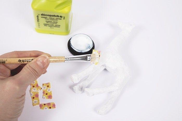 ETAPE 2/8 Déchirez ou découpez quelques morceaux de papier d'environ 1cm x 1cm. Appliquez le vernis colle sur le support à décorer.