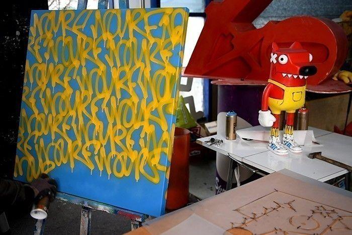 ETAPE 5/10 Bomber un fond de couleur bleu avec la Bombe de peinture Acrylique GOLD Bleu et écrire le mot Nourf© avec la Bombe de peinture Acrylique GOLD Jaune. Faire des « splashs » avec la Bombe de peinture Acrylique GOLD Noir. Astuce : Pour faire des splashs, pulvériser dans un culot de bombe de la peinture et projeter.