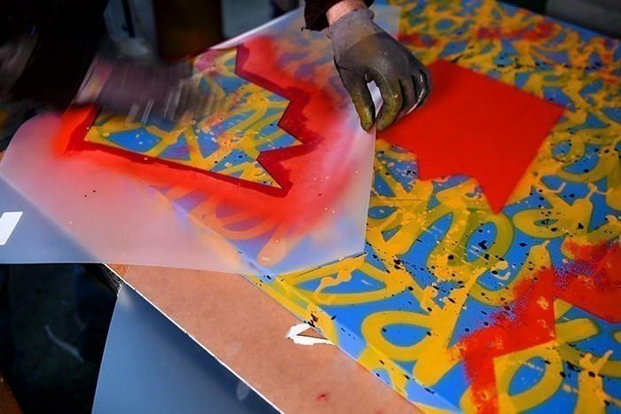 ETAPE 6/10 Utiliser le pochoir pour le fond de visage de Nourf© en bombant avec la bombe de peinture Acrylique Rouge. Retourner ensuite le pochoir et le plaquer à différents emplacements de la toile.
