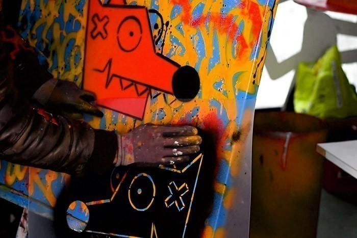 ETAPE 7/10 Positionner le pochoir pour la couleur noire sur le visage de Nourf© et bomber avec la bombe de peinture Acrylique Noire. Retourner ensuite le pochoir et le plaquer à différents emplacements de la toile.