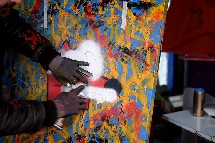 ETAPE 8/10 Positionner le pochoir pour la couleur blanche sur le visage de Nourf© et bomber avec la bombe de peinture Acrylique Blanche.