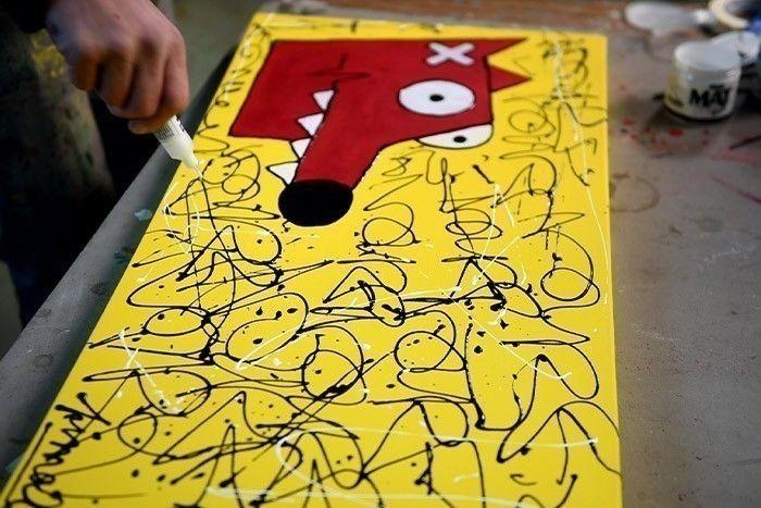 ETAPE 8/8 Avec le marqueur Pébéo Mat Pub de couleur noire, écrire le mot Nourf© sur la face et les côtés de la toile. Faire des « splashs » en projetant de la peinture avec les différentes couleurs.