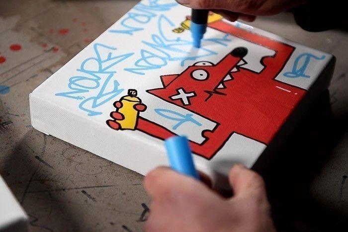 ETAPE 4/8 En utilisant le Paint Marker Posca Bleu, écrire son nom Nourf© pour personnaliser le fond de la toile.