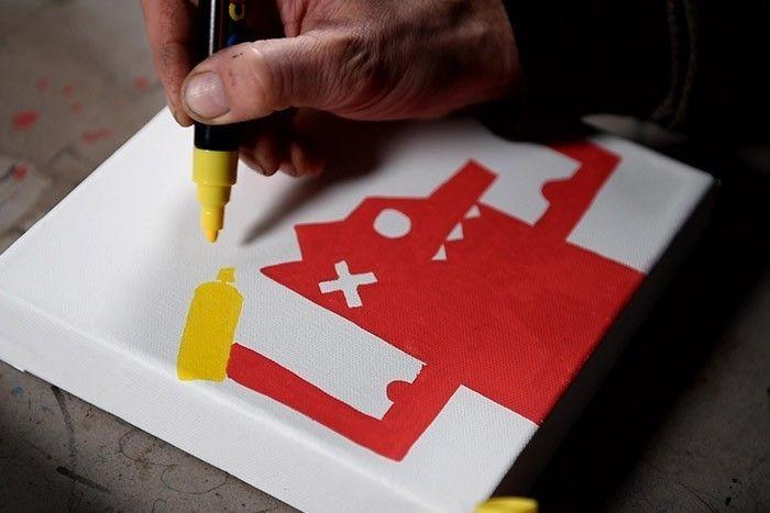 ETAPE 2/8 En utilisant le Paint Marker Posca jaune, dessiner les bombes de peinture dans ses mains.