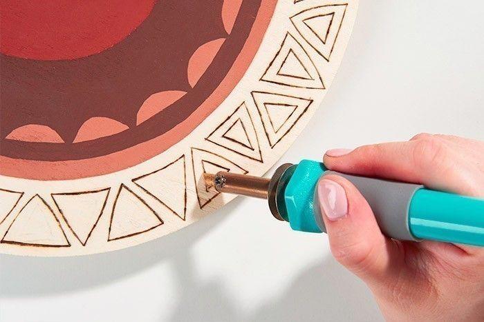 ETAPE 4/8 Positionner la pointe universelle sur le pyrograveur et la visser à l'aide de la pince. Brancher le pyrograveur et le laisser chauffer. Commencer par pyrograver avec la tranche de la pointe le contour des triangles en suivant les repères décalqués.