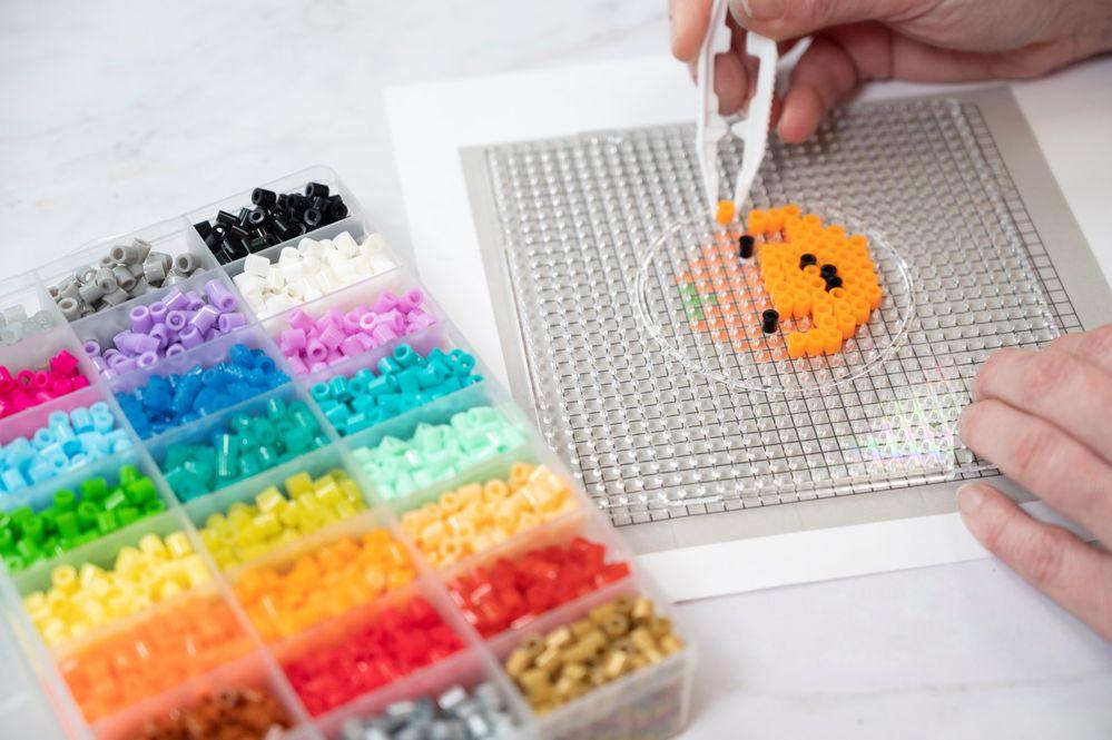 1. Télécharger et imprimer les gabarits. Poser une grille transparente sur un gabarit et créer le motif en plaçant les perles à repasser à l'aide de la pince sur les picots plastique.