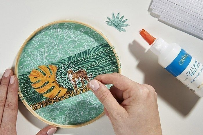 6. Encoller le rond de papier sous l'anneau intérieur. Coller harmonieusement les embellissements sur la ficelle.