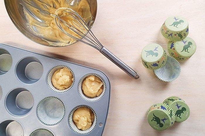 4. A votre préparation précédente, rajouter la farine et la levure et mélanger à la main jusqu'à obtenir une pâte uniforme. Placer les caissettes dans votre moule à cupcake et les remplir à mi hauteur. Cuire durant 12-15min à 180°. Laisser refroidir.