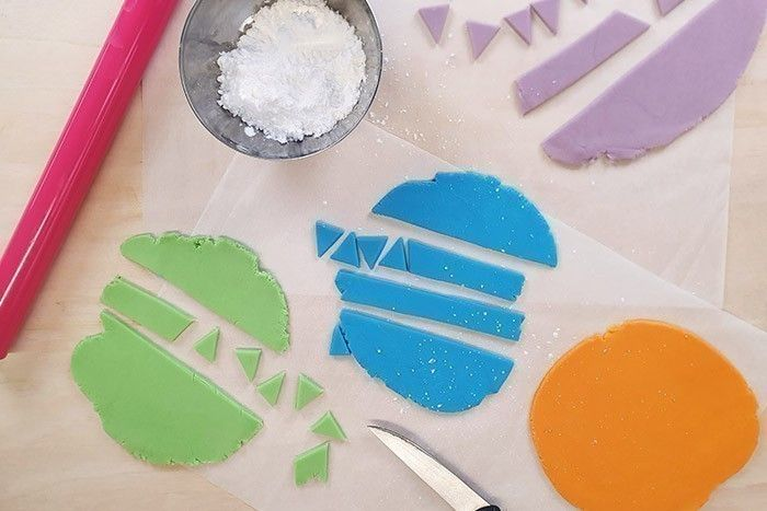 6. Etaler la pâte à sucre sur 0,5cm sur le papier cuisson et la détailler en bandes puis en triangles. Si elle colle, ne pas hésiter à saupoudrer de sucre glace dessus.