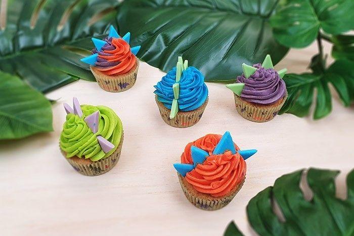 8. Choisir la couleur désirée, placer la poche pleine dans la poche vide et former un joli pochage en spirale sur le dessus du cup cake. Puis changer de poche colorée pour une autre couleur, ainsi de suite. Planter ensuite les triangles de pâte à sucre pour former les crêtes des dinosaures.