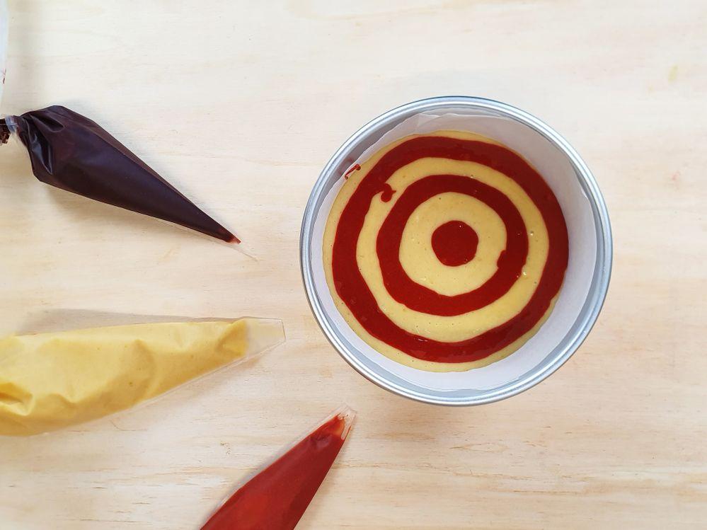3. Diviser la pâte à cake en trois et en colorer deux, une en orange et l'autre en marron. Placer les trois pâtes dans des poches à douilles. Recouvrir le fond du moule de la moitié de la pâte « nature », puis former 3 cercles avec la pâte orange.