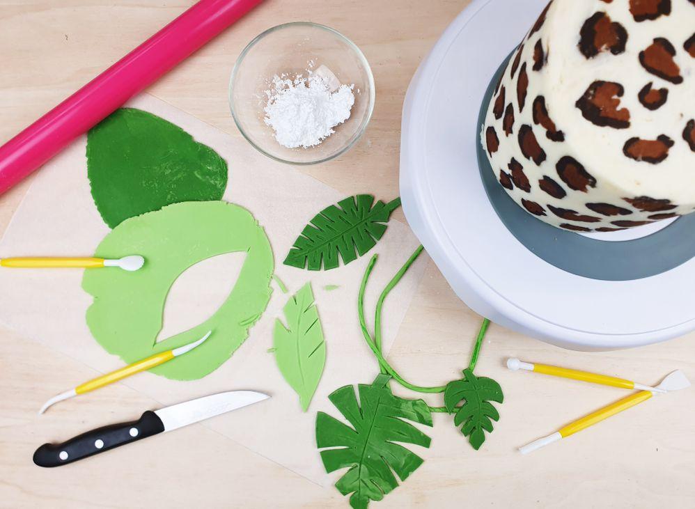 7. Placer la bande tachetée sur le cake et appuyer pour la faire adhérer puis retirer le papier cuisson. Etaler de la pâte à sucre avec votre rouleau et découper dedans des feuilles de tailles et formes différentes. Dessiner les rainures des feuilles avec les outils de pâte à sucre. 