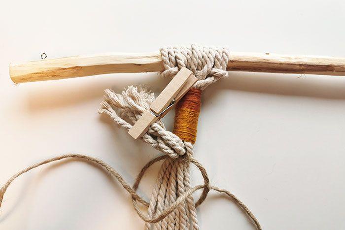 4. Utiliser une pince à linge pour isoler les 6 fils de macramés courts. Nouer le fil de jute sous le tissage coloré et commencer à tisser sur environ 20 cm des nœuds plats sur tous les fils blancs (brins porteurs