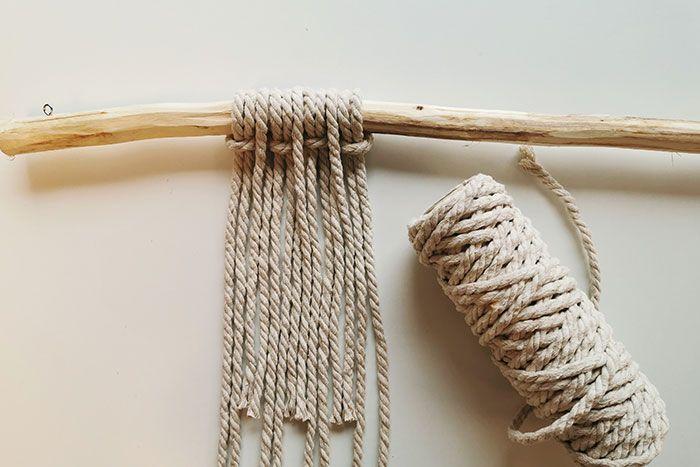 2. Plier en deux tous les fils et réaliser 4 nœuds à tête d'alouette sur le bâton de suspension avec les longs fils macramé blancs. Insérer entre chaque les fils blancs plus courts.